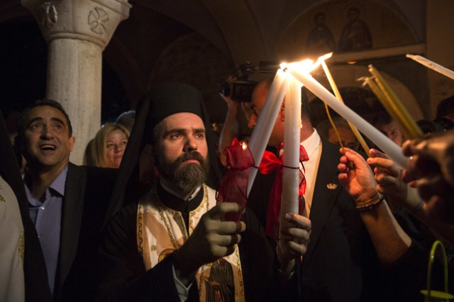 "A Greek Orthodox priest lights the candles of faithful with Holy Fire brought from Jerusalem outside a church in Athens, on Saturday, April 30, 2016. Across the world, Orthodox Christians are celebrating Easter, commemorating the day followers believe that Jesus was resurrected more than 2,000 years ago. In Greece, the faithful attended Easter Mass holding candles lit with ""Holy Fire"" from the Church of the Holy Sepulchre in Jerusalem. (AP Photo/Yorgos Karahalis)"